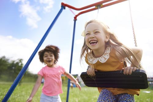 stock photo of two little girls laughing and playing on a play set outside